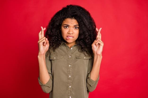 Meisje met gekruiste vingers bijtende lippen ik met krullend golvend bruin haar geïsoleerd