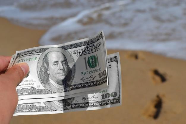Meisje met geldrekening van 300 dollar op de achtergrond van de zee oceaan