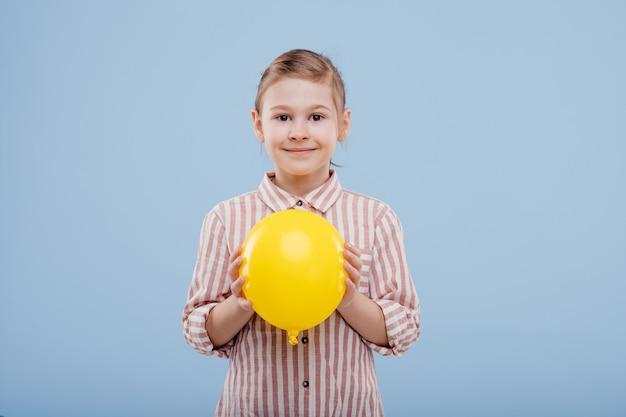 Meisje met gele ballon. kijkt naar de camera, gekleed in gestreept shirt, geïsoleerd op blauwe achtergrond, kopieer ruimte