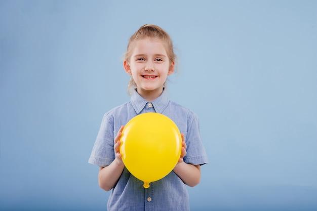 Meisje met gele ballon met glimlach. kijkt naar de camera, geïsoleerd op een blauwe achtergrond, kopieer ruimte