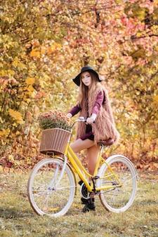 Meisje met gele fiets in de herfst op een wandeling.