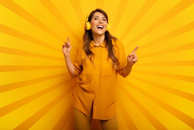 Meisje met gele hoofdtelefoon luistert naar muziek en dansen. emotionele en energetische expressie