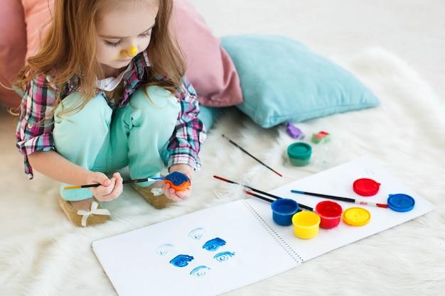 Meisje met gele neus schildert speelgoed in blauwe kleur