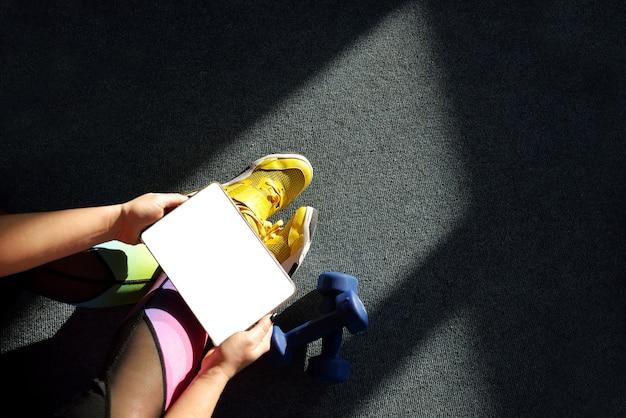 Meisje met gele sneakers houdt een tablet met gewichten rond voor training. online leerconcept.