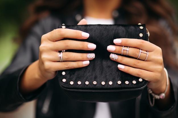 Meisje met gemanicuurde nagels met mooi ornament in trouwringen die zwarte bontzak houden.