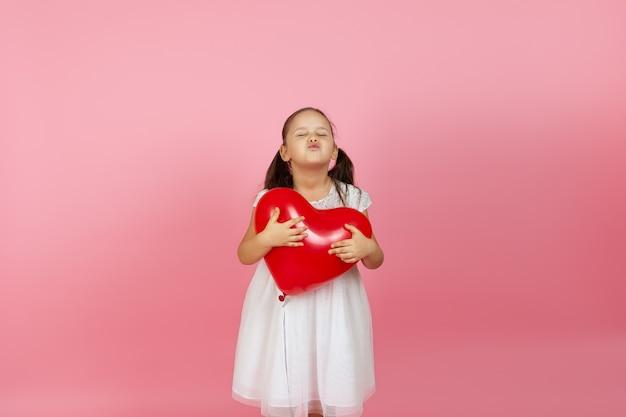 Meisje met gesloten ogen in een witte jurk houdt een rode ballon vast en blaast een kus