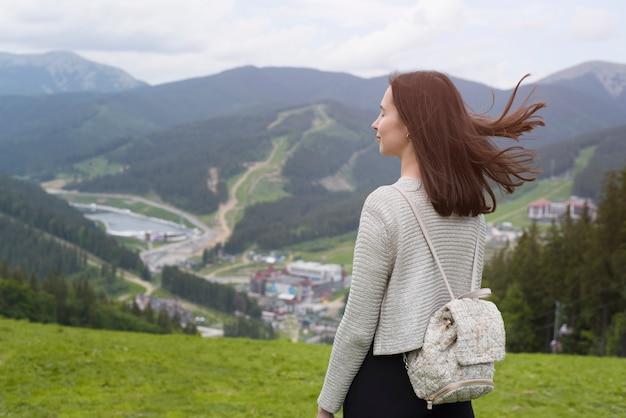 Meisje met gesloten ogen staat op een heuvel. stad in de verte