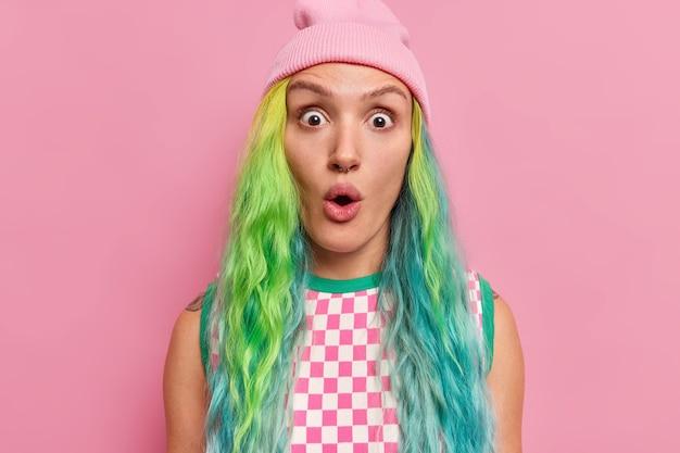 Meisje met geverfd lang haar piercing in neus staart verrassend naar camera houdt mond open draagt hoed geruite jurk geïsoleerd op roze