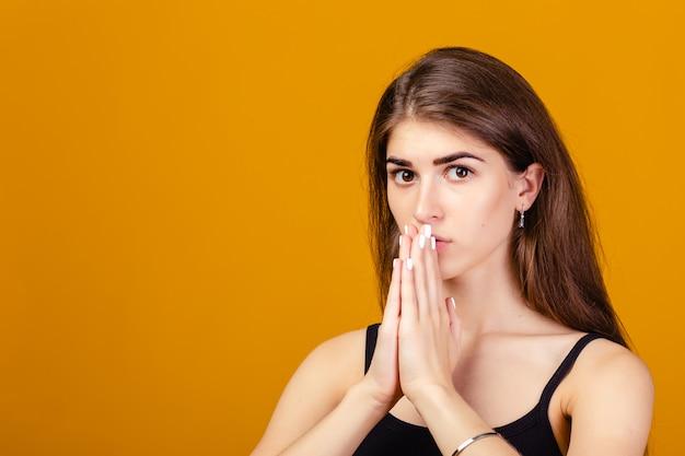 Meisje met gevouwen handen om hulp of vergeving te vragen