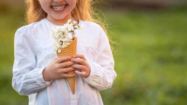 Meisje met gevulde wafelkegel, bloeiende kersentakken, die haar hand houden