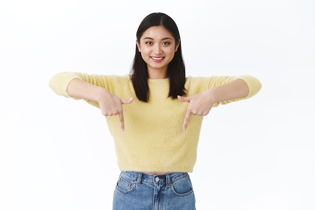 Meisje met geweldige productkorting, geweldige evenementpromo, bedrijfspaginabanner. mooie aziatische vrouw in gele trui die uitnodigt tot een advertentie die met de vingers naar beneden wijst en glimlacht