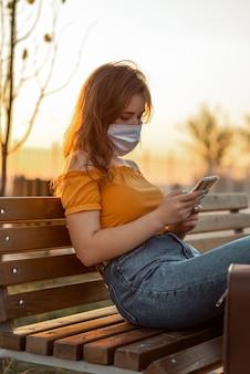 Meisje met gezichtsmasker met behulp van telefoon zittend in park met haar koffer