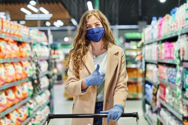 Meisje met gezichtsmasker teken duimen omhoog en boodschappen in de supermarkt kopen tijdens pandemie.
