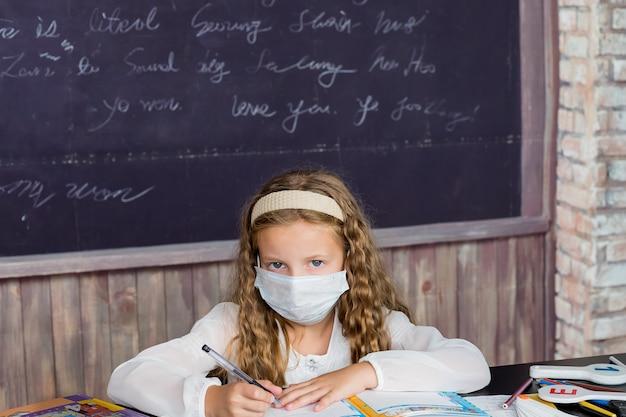Meisje met gezichtsmasker terug op school na covid quarantaine en lockdown schoolmeisje schrijven in oefening