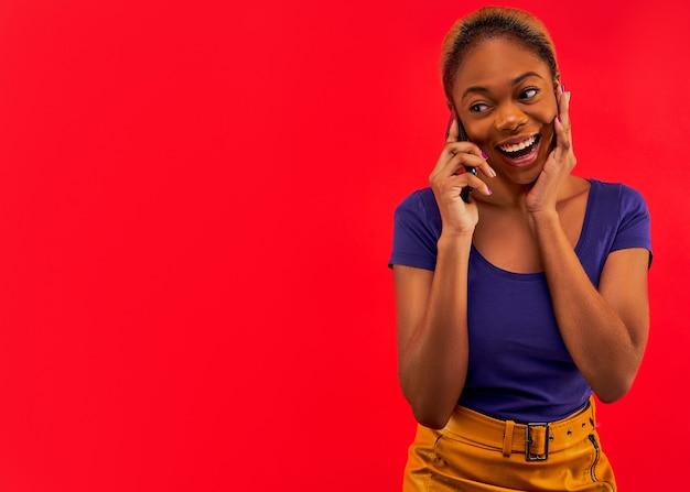 Meisje met glimlach in een blauw t-shirt in een gele rok met oorringen met smartphone in haar hand