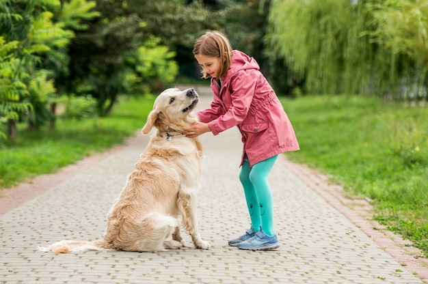 Meisje met golden retriever wandelen in groen park
