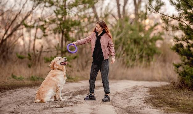 Meisje met golden retrieverhond in het bos