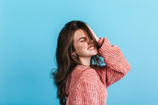 Meisje met golvend donker haar lacht. close-upportret van vrouw in zachte sweater en bronzenoorringen.