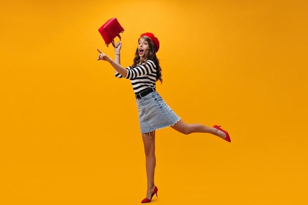Meisje met golvend haar naar plaats voor tekst wijzen en tas vasthouden. koele jonge vrouw in moderne denimrok en het rode hielen stellen.