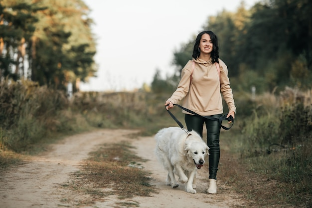Meisje met gouden retrieverhond die op bospad loopt