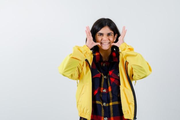 Meisje met grappig gebaar in geruit overhemd, jasje en schattig op zoek