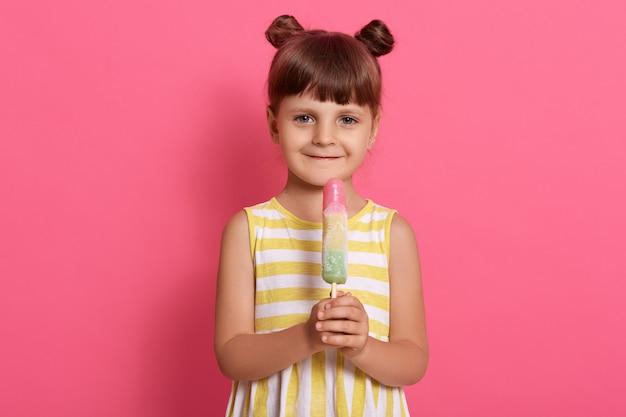 Meisje met groot fruitijs dat zich op roze muur bevindt, zomeroutfit draagt, twee knopen heeft, positieve emoties uitdrukt.
