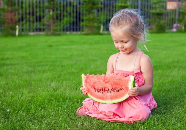 Meisje met groot stuk van watermeloen in handen op groen gras