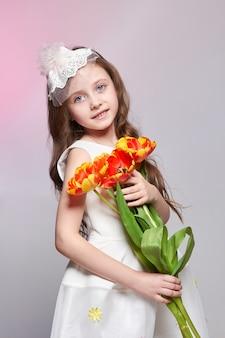 Meisje met grote blauwe anime-ogen en een boeket tulpenbloemen in haar handen. wereld moederdag, lentedag, lenteboeket in handen van het kind. lang krullend blond haar