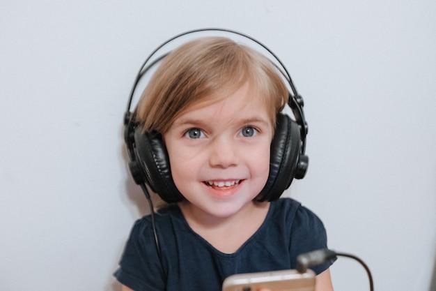 Meisje met grote hoofdtelefoons thuis