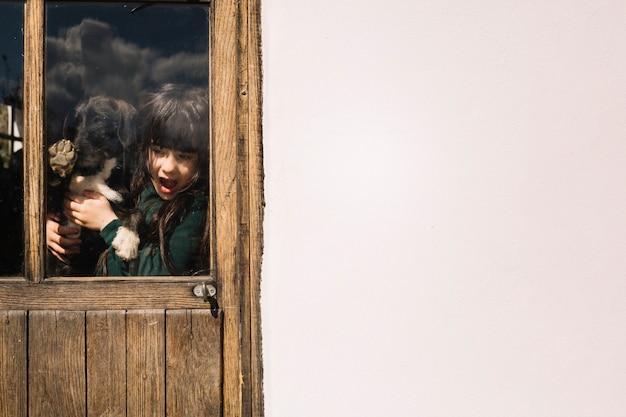 Meisje met haar die hond door transparante glasdeur wordt gezien