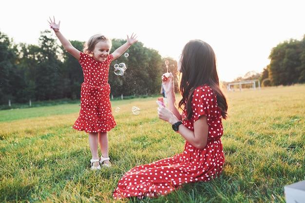 Meisje met haar dochter die plezier heeft met de bubbels buiten zittend op het gras