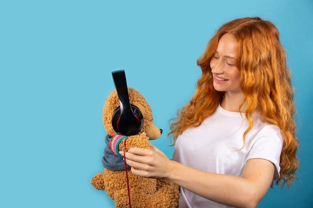 Meisje met haar geliefde beer. het meisje zette een koptelefoon op de beer, poseerde en glimlachte. foto op een blauwe muur met een lege zijruimte.