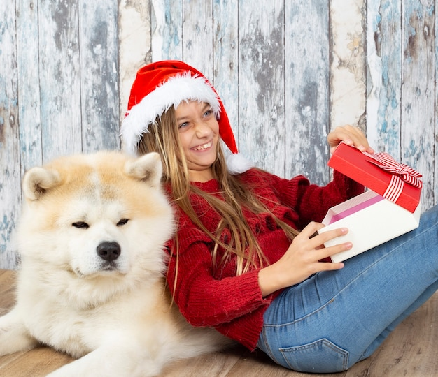 Meisje met haar hond en kerstmuts, cadeau openen