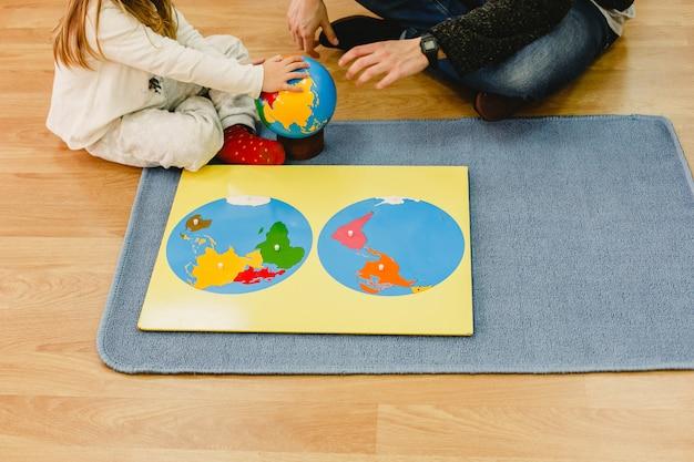 Meisje met haar leraar met behulp van montessori-materialen om de geografie van de wereld te bestuderen met een kaart