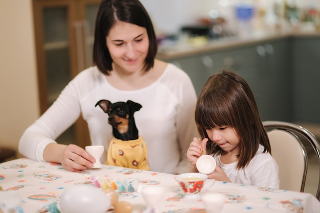 Meisje met haar moeder bereidt zich voor op pasen en print eieren die ze bij de tafel zitten en hebben