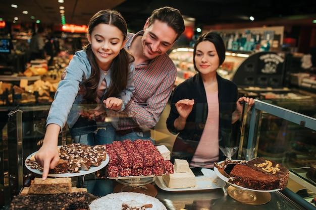 Meisje met haar ouders bij supermarkt oppakken van een taart