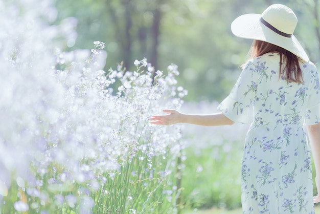 Meisje met haar rug en strohoed op een gebied van bloemen, gelukkige aziatische vrouw