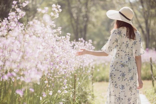Meisje met haar rug en strooien hoed op een gebied van bloemen