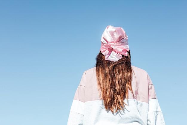 Meisje met haar rug gedraaid met een roze hoofddoek. internationale borstkankerdag, met de lucht op de achtergrond.