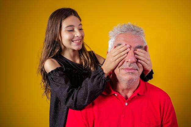 Meisje met haar vader gesloten ogen. gele achtergrond. vaderdag. braziliaanse familie.