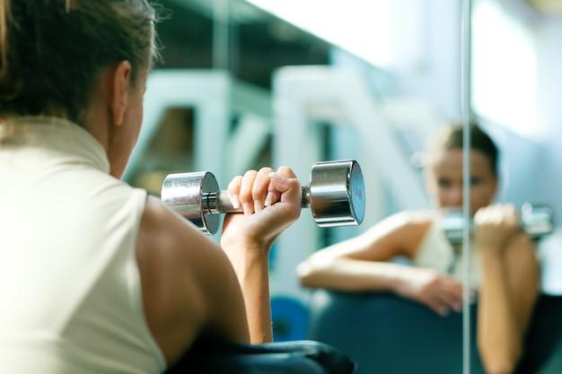 Meisje met halters weerspiegelen in de spiegel