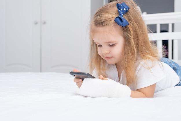 Meisje met hand in cast tot in bed met smartphone, cartoon of onderwijsvideo kijken.