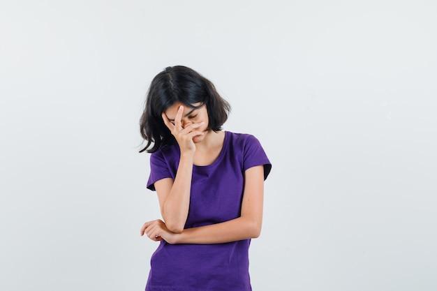 Meisje met hand op gezicht in t-shirt en vermoeid op zoek. vooraanzicht.