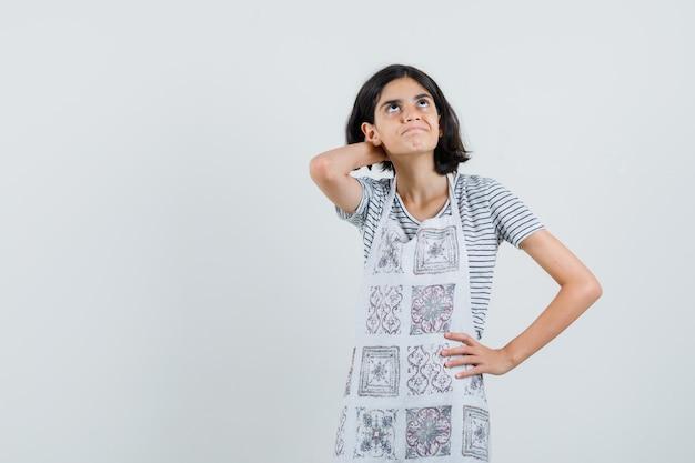 Meisje met hand op nek in t-shirt, schort en peinzend op zoek.