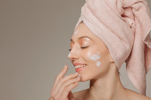 Meisje met handdoek op het hoofd met behulp van lotion