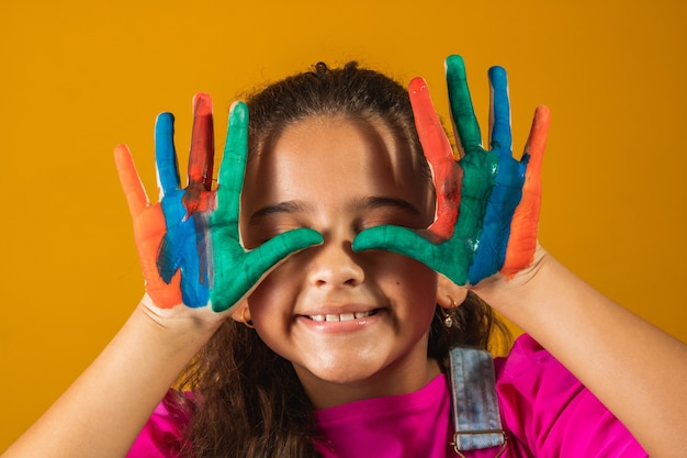 Meisje met handen geschilderd in gekleurde verf. meisje met handen op ogen geschilderd