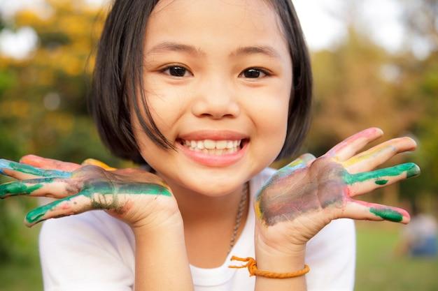 Meisje met handen geschilderd in kleurrijke verf