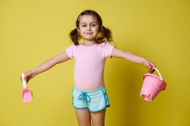 Meisje met hark en schop in uitgestrekte handen glimlachend camera poseren op gele muur met kopie ruimte te houden