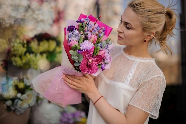 Meisje met heel schattig boeket in roze papier