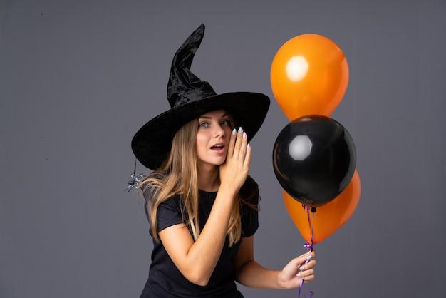 Meisje met heksenkostuum voor halloween-feest en iets fluisteren